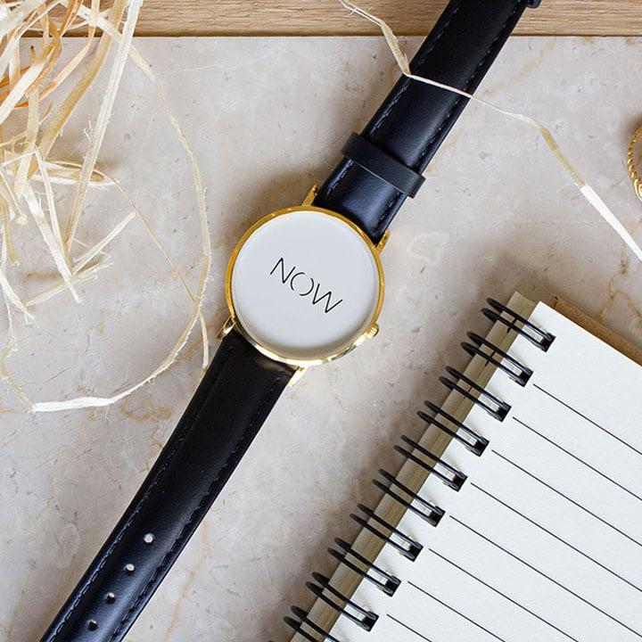Zwarte Watch Now Fine Collection flatlay naast een notitieblock
